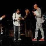 Paola d'Agnese consegna il Premio De André, sezione Poesia, al vincitore, Mariano Macale. Sul palco anche Piero Cademartori (a sinistra) e Massimo Cotto (a destra)